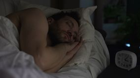 Bearded man sleeping on sofa bed, clock standing on night table, late night rest