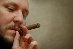 Bearded man smokes cigar Stock Photos