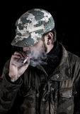 Bearded man smokes a cigarette in Finland. Bearded man smokes a cigarette. The man has a camouflage jacket and camouflage cap. The eyes are hidden under a Stock Photos