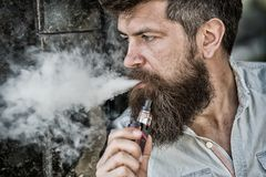 Bearded man smokes vape, white clouds of smoke. Electronic cigarette concept. Man with long beard looks relaxed. Man. With beard and mustache on calm face, dark Royalty Free Stock Image