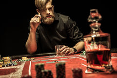 Bearded man smoking cigar and drinking whisky while playing poker Stock Photography