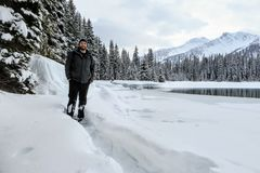 A bearded man snowshoeing around Island Lake in Fernie, British Columbia, Canada. The majestic winter background is a beautiful place to go hiking or stock photography