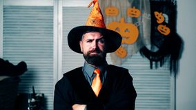 Bearded man in sorcerer`s suit raises his eyebrows. Halloween party and celebration concept. Bearded man in sorcerer`s suit raises his eyebrows. Halloween party stock footage