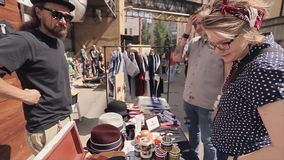 Bearded man stand at counter of street shop with hats, gloves, tub, banks. Buyers. Summer sunny day stock footage
