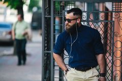 Bearded man standing and listening to music Royalty Free Stock Images