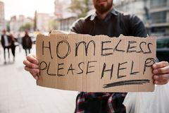 Bearded man is standing on street and holding a cardboard. It says homeless please help. Guy is looking for some mercy. From other people and help as well royalty free stock images