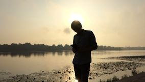 Bearded Man Stands And Looks at His Smartphone at the Dnipro at Sunset in Slo-Mo. A Sportive Young Man Looks at His Smartphone in Summer in Slo-Mo. he Stands on stock footage