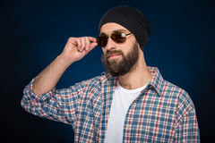 Bearded man. Stylish bearded man in a cap and glasses. Blue background Royalty Free Stock Images