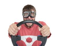 Bearded man in stylish goggles with steering wheel isolated on white background, car driver concept stock photography