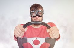 Bearded man in stylish goggles with steering wheel on smoke background, car driver concept. stock photo