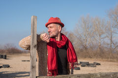 Bearded man in a stylish hat stands next to old wooden fence Royalty Free Stock Images