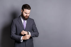 Bearded man in suit adjusting sleeves copy space Royalty Free Stock Images
