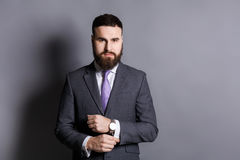 Bearded man in suit adjusting sleeves copy space Stock Photo