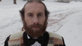 Bearded man in a suit and bow tie on a background of winter stock footage