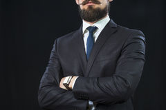 Bearded man in suit crossing his arms on chest. Horizontal view Stock Photo