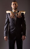 A bearded man in a suit and the woman& x27;s hand with red nail polis. H. Stylish man in a suit and tie on gray background royalty free stock photos