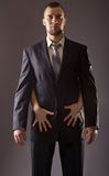 A bearded man in a suit and the woman& x27;s hand with red nail polis. H. Stylish man in a suit and tie on gray background stock photos