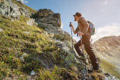 A bearded man in sunglasses and a cap with a backpack stands on top of a rock and looks into a rocky valley high in the