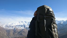A bearded man in sunglasses hat with a backpack and a camera stands high in the mountains and looks on the sidelines. Against the backdrop of snow-capped stock footage