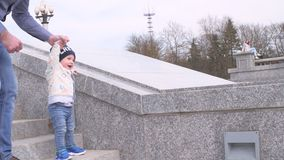 Bearded man in sunglasses holding his little son by the hand helps the happy baby boy to go down the granite ladder step. Slo motion video of a bearded man in stock video footage