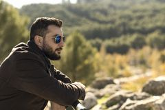 Bearded man with sunglasses supported on a railing looking tonat Royalty Free Stock Images