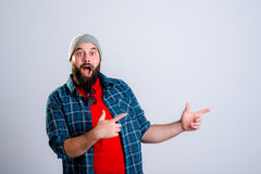 Bearded man is surprised and pointing to the side Royalty Free Stock Images