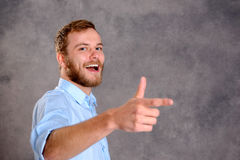 Bearded man is surprised and pointing to the side Stock Photos