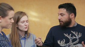 A bearded man in a sweater, gesturing, urges two girls in expediency of his decision stock video footage