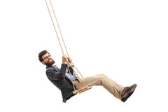 Bearded man swinging on a swing. And looking at the camera isolated on white background Stock Photography
