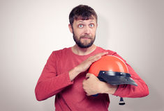 Bearded man in a T-shirt holding a red motorcycle helmet Royalty Free Stock Photography