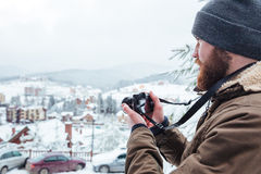 Bearded  man taking pictures of view outdoors in winter. Concentrated bearded young man taking pictures of view outdoors in winter Royalty Free Stock Photography