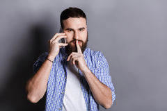 Bearded man talking on phone point be quiet. Young guy having important conversation, showing hush sign with finger on lips, gray studio background, copy space Stock Photos
