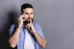 Bearded man talking on phone point be quiet. Young guy having important conversation, showing hush sign with finger on lips, gray studio background, copy space Royalty Free Stock Photos