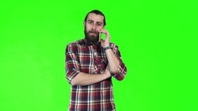 Bearded man talking on smartphone. On green screen stock video