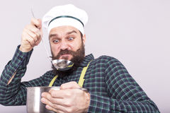 Bearded man tasting  soup with a ladle with an expression of dis Royalty Free Stock Images