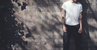 Bearded man with tattoo wearing blank white tshirt and black jeans. Bricks wall background. Wide mockup. Bearded man with tattoo wearing blank white tshirt and Stock Photos