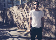 Bearded man with tattoo wearing blank white tshirt and black sunglasses. City garden wall background. Horizontal mockup Stock Photography