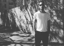 Bearded man with tattoo wearing blank white tshirt, sunglasses. City street background. Horizontal mockup. Black and Royalty Free Stock Photography