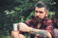 Bearded man with tea or coffee cup in forest. Tourist in plaid shirt hold mug. Hipster with long beard relax on natural. Green landscape. Camping, drinking and royalty free stock photos