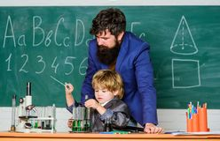 Bearded man teacher with little boy. father and son at school. Pupil kid in the chemistry class confidence charisma royalty free stock image