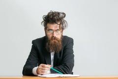 Bearded man teacher at table Stock Photos