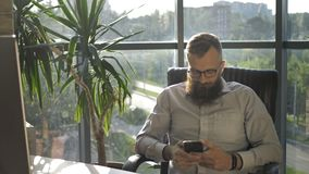 Bearded man texting in the mobile phone in modern loft coworking.  stock video footage