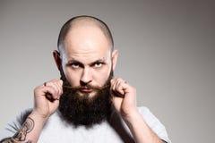 Bearded man touching his beard Stock Photography