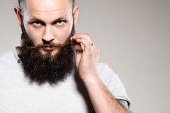 Bearded man touching mustache Stock Photo