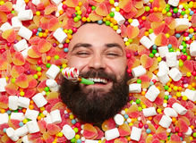 Bearded man with toy flute and candies Stock Image