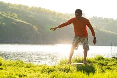 Bearded man is training on the balance board. On a green meadow next to river in the rays of summer sun. Back light, front view Stock Photography