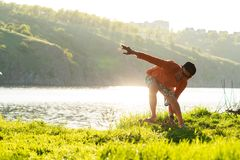 Bearded man is training on the balance board on a green meadow. Next to river in the rays of summer sun. Back light, front view Royalty Free Stock Images