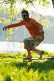 Bearded man is training on the balance board and having fun. On a green meadow next to river on sunny evening. Back light Stock Image