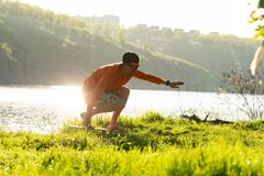 Bearded man is training on the balance board and having fun. On a green meadow next to river in the rays of summer sun. Back light Royalty Free Stock Photo
