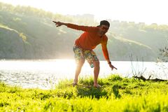 Bearded man is training on the balance board and having fun. On a green meadow next to river in the rays of summer sun. Back light, front view Royalty Free Stock Image